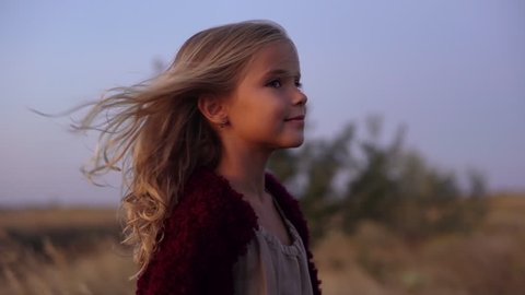 round footage of cute caucasian blondie girl wearing soft red cardigan standing in the middle of field, looking on camera enjoying wind blowing her hair early in morning slow motion