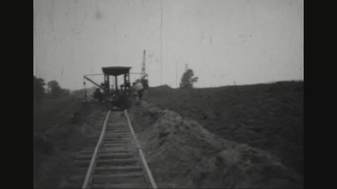 CIRCA 1931 - A bulldozer, a train and a dragline excavator are used in the construction of a leve on the Mississippi River in Duckport, Louisiana.