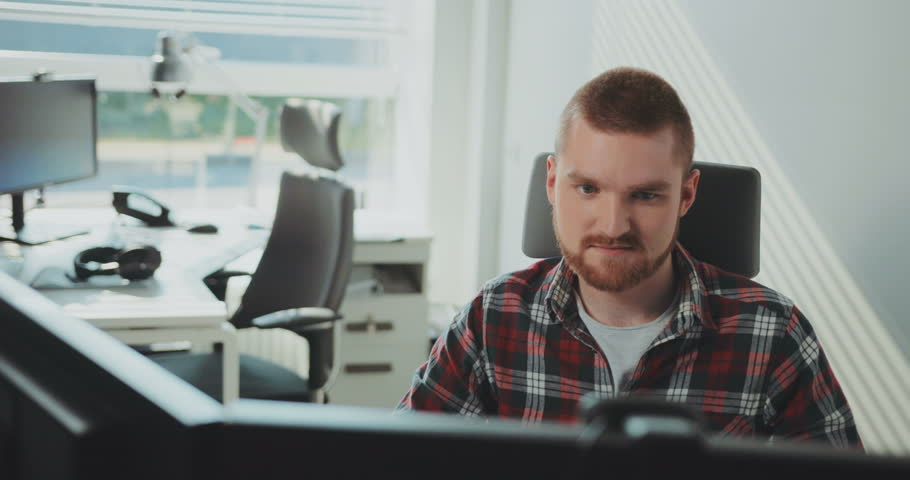 A young bearded man sits at a computer. Works in the office. Contemporary design. Designer, computer, office, technology, business, indoors, male. Shot on RED Epic Camera. | Shutterstock HD Video #31727647