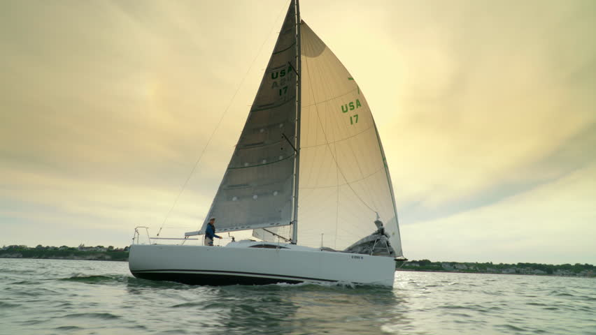 Experienced solo sailor sailing on the ocean in a racing sailboat.  Shot from chase boat at low angle at sunset.