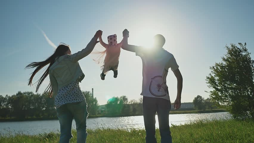 Happy young family with daughter in the grass by the lake. Parents hold their daughter by both hands and raise them high. Happy together in the rays of sunset.