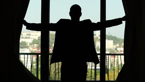 Man expand both hands, open curtain, stand and look outside, sunny city seen blurred outdoors. Medium telephoto lens, half length view from back, black silhouette of guy in suit