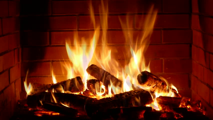 Impressive satisfying close up shot of wood burning slowly with orange fire flame in cozy brickwork fireplace atmosphere