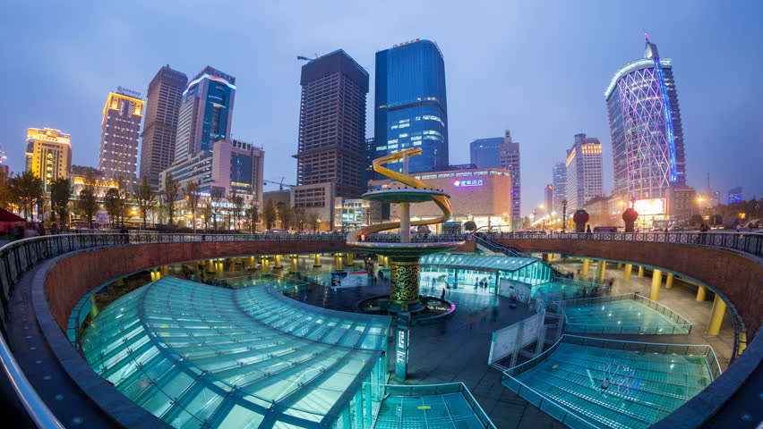 CHENGDU - NOV 21: Timelapse view over the city centre with a subway station exit in the foreground, on November 22 in Chengdu, China