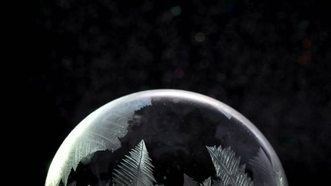Freezing Snow globe snowflakes. Winter Background. For Christmas and New Year Holidays precious backdrop. Ice patterns frosting on ball of soap against black abstract background.