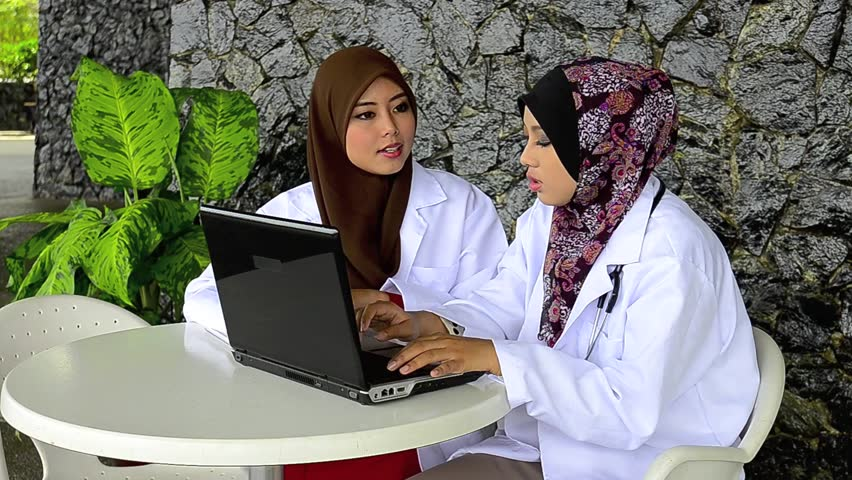 Confident Muslim female doctor busy study case