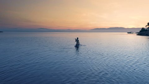 Aerial Shot of a Beautiful Woman with on a Standup Paddleboard. Woman Silhouette with Pink Sunset and Coastal Hills Visible Shot on Phantom 4K UHD Camera.