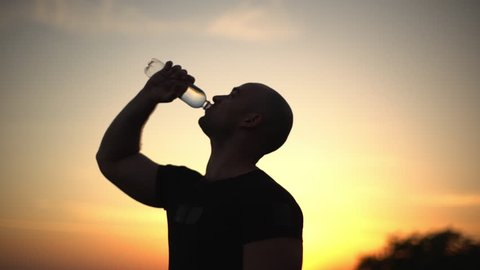 closeup slow motion side view silhouette of caucasian bald muscular guy drinking water from plastic bottle, after doing workout on nature with colourful sunrise background