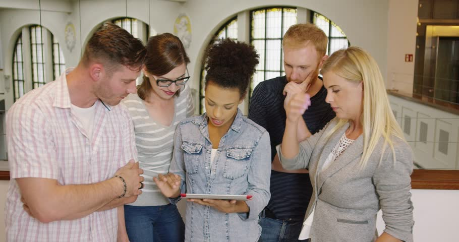 Group of people in casual clothes looking at ideas on tablet screen and smiling during discussion of new project. | Shutterstock HD Video #31848427