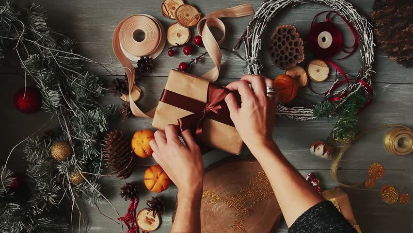A top-down plan. Fully visible the table with the decorations. Female hands put and finalize Christmas gift wrapped in craftool paper on a wooden table. Bandaging tape and tied in a bow.