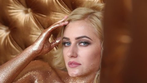 Portrait of a naked girl with skin covered in gold sequins and a professional make-up on a golden background.