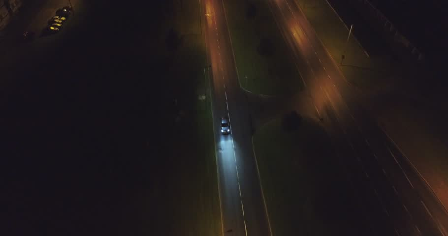 Camera follows cars, on the road at night. Aerial footage. An amazing aerial view of Kohtla-Jarve City at night, Estonia.