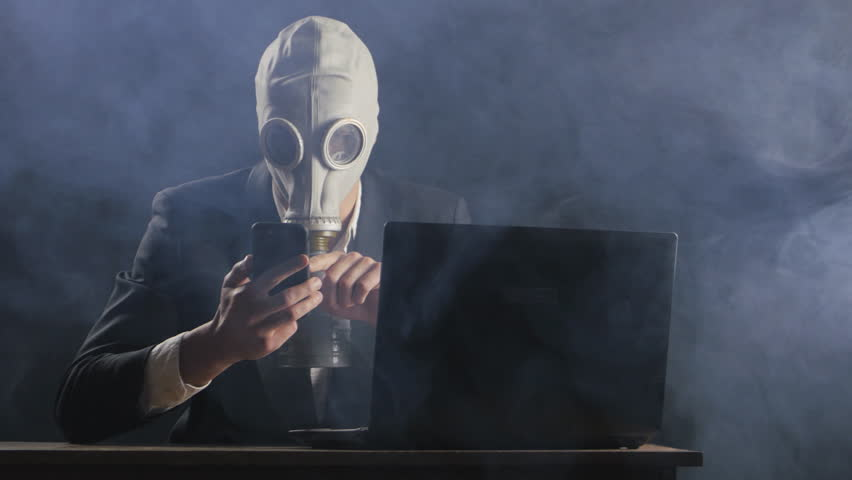 Businessman wearing gas mask working at smartphone in dark office