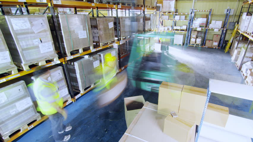 Time-lapse clip of workers in a warehouse in high visibility clothing and hard hats. They are moving boxes around and using a forklift truck to manoeuvre heavy stacks of goods around.