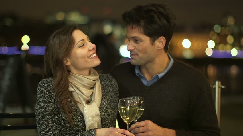 An attractive casually dressed couple are drinking wine at an open air terrace in the city at night. They are very intimate and the lights of the city can be seen in the background