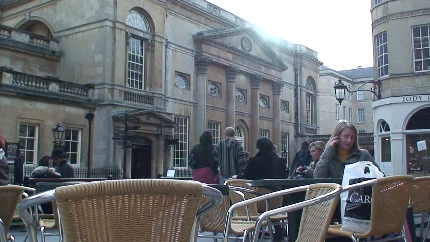 BATH, SOMERSET, UNITED KINGDOM - CIRCA 2011: Woman sits at cafe tables across from the Roman Baths in Bath, Somerset.