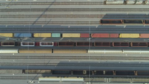 AERIAL TOP DOWN: Flying above empty cargo train moving past freight containers at industrial railroad station on sunny day. Empty railroads and export container trains on industrial railway terminal.