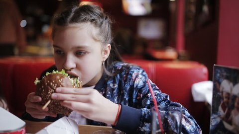 little girl teenager eats a burger in fast food. hamburger and french fries
