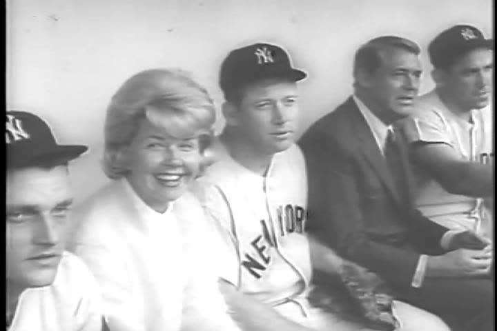 CIRCA 1960s - Doris Day and Cary Grant sit in the Yankees dugout in 1963, along side Mickey Mantle, Yogi Berra, and Roger Maris, the cast of the hit movie, The Touch of Mink, at Yankee Stadium, NYC