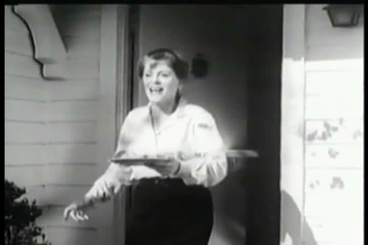 CIRCA 1950s - A woman with a headache scolds neighborhood boys before taking Anacin and giving them cookies, in a television commercial, in the 1950s. | Shutterstock HD Video #31919905