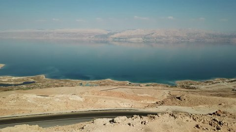 Aerial View of the Dead Sea from a cliff facing Jordan with red mountains in the background
