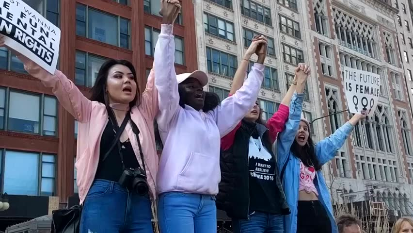"""CHICAGO, IL-January 21, 2017. Women's March. A group of young women of various races chanting """"No hate, No fear, Everyone is welcome here"""" and holding signs. Sanctuary City, Immigration."""
