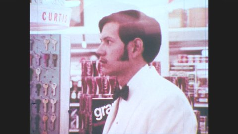 1970s: Teenager stands at check out counter, clerk sides beer back to teenager. Teenager smiles.