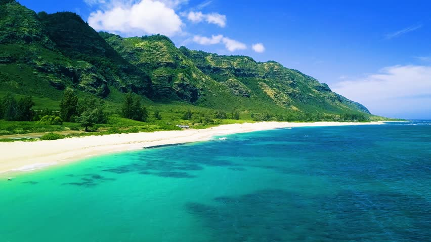 Aerial View of Erdman Beach, Kaena Point Oahu Hawaii. Tropical blue ocean, dry steep mountain cliffs, blue skies with clouds. Sea waves on reef to white sand beach. Green foliage, 4K UHD drone. Sexy.