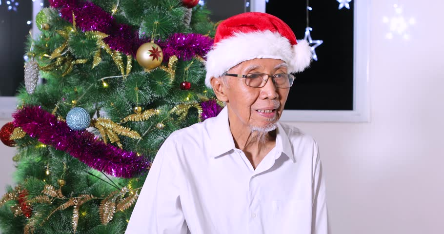 Happy grandfather wearing Santa hat and getting a Christmas gift from his granddaughter near a Christmas tree at home, shot in 4k resolution | Shutterstock HD Video #31965016