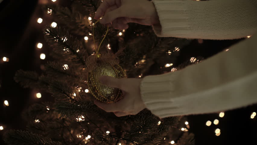 woman decorating the gold christmas ball on a christmas tree with bokeh lights background - Gold Christmas Tree Lights