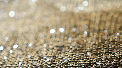 fabric as background. 4k, slow motion, gold knitted fabric with paillettes. blurring