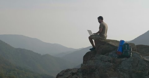 A man uses computer on top of a mountain and behind a magnificent landscape. Concept of: unlimited internet surfing, freedom, unlimited technologies.