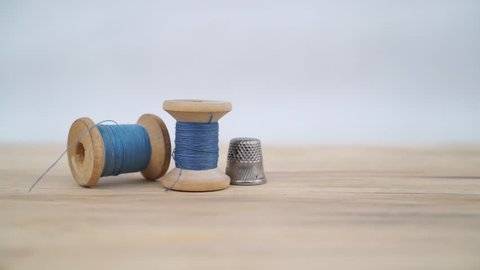 Old spool of blue thread with needle and sewing thimble. Still image.Tailor's work table. textile or fine cloth making.
