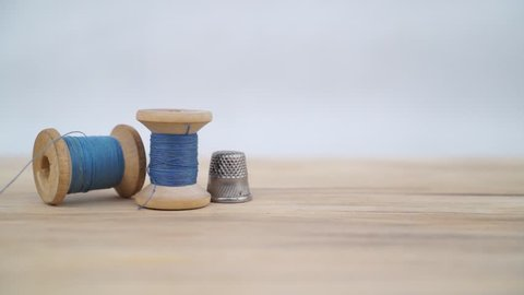 Old spool of blue thread with needle and sewing thimble. Tailor's work table. textile or fine cloth making.