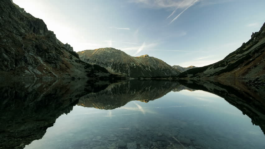 Time lapse reflection of clouds and shadow monsters in lake Morskie Oko, Tatra mountains, Poland landscape background timelapse