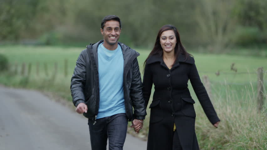 An attractive couple holding hands and enjoying a walk down a country lane. Slow motion | Shutterstock HD Video #3204115