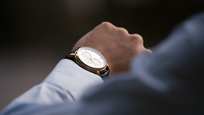 Young male business man is waiting for a meeting. Hand with a clock close up. Waits. Looks at the clock, time.