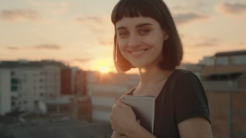 Playful beautiful young woman in her 20s, with short haircut and trendy hipster tattoos stands in warm summer sunset light, holds tablet device, chuckles and smiles into camera, shows tongue