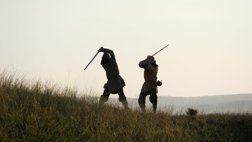 Silhouettes of two warriors Viking are fighting with swords. Contre-jour