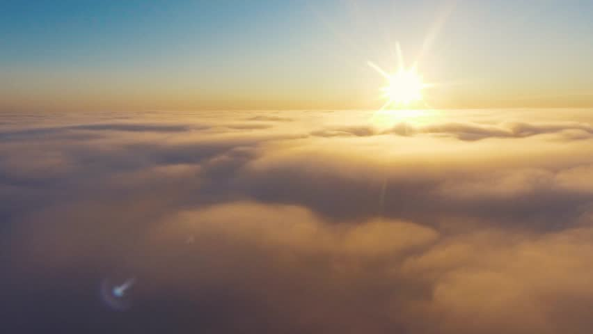 Aerial View. Flying in fog, fly in mist. Aerial camera shot. Flight above the clouds towards the sun. Misty weather, view from above. Birds point of view