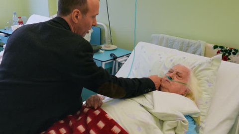 Man is visiting old, ill lady in hospital