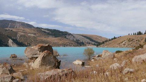 Tilt up of the emerald Big Almaty Lake in autumn season.