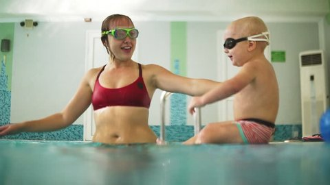 Cute blonde toddler in protective glasses is diving under the water together with his mother in the swimming pool trying to take out his toy. His mother is teaching him how to swim. An underwater shot