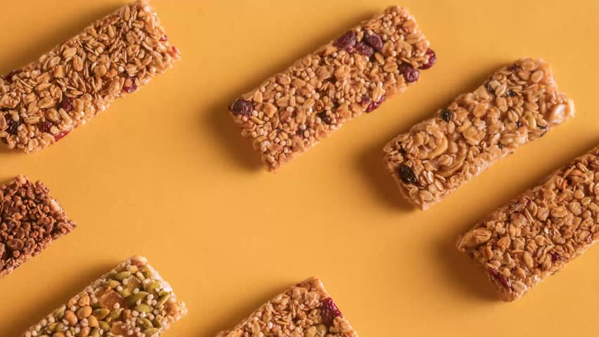 Different flavor granola bars moving along a solid orange background stop motion top view