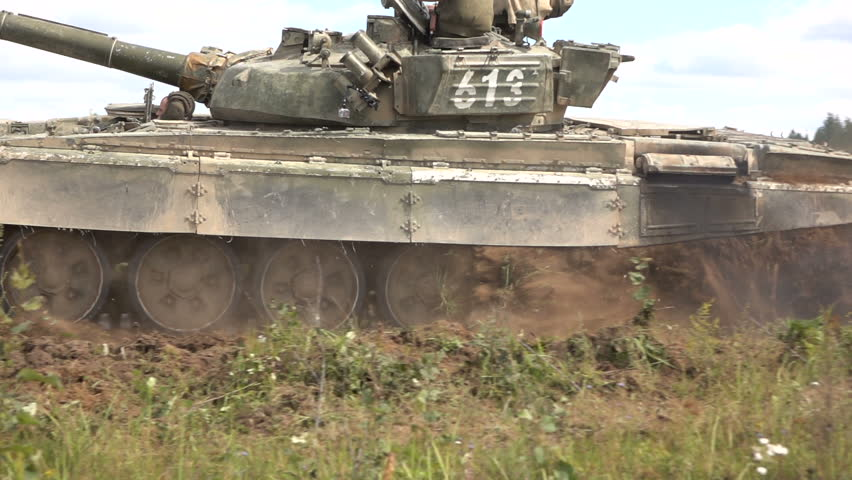 Tank rides on the field. Slow Motion.