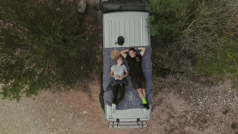 Top view on romantic couple on date, laying on roof of car or van, watch stars or sky in natural national park, secluded camping site in wilderness, concept relationship goals or millennials