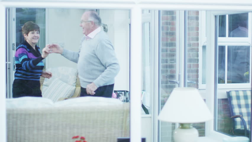 A happy and lively mature caucasian couple show that they still have plenty of energy as they laugh and dance together at home. Shot from the outside looking in and in slow motion.