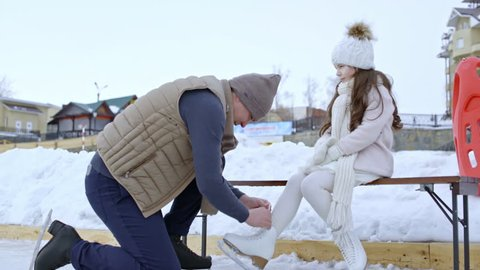 PAN of man wearing warm hat and puffy jacket tying ice skates for cute little girl, then skating together on outdoor rink in winter