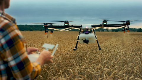 Man controling the agriculture drone flying. Shot in Red Epic Dragon