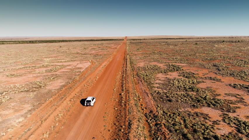 Drone shot vehicle traveling dusty road in Australian Outback.